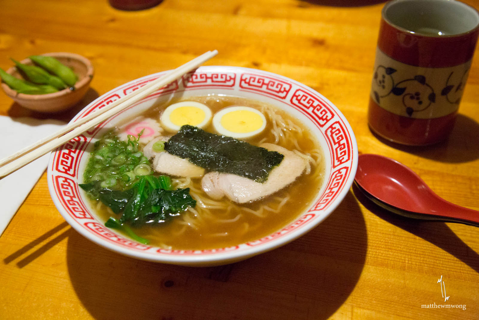 Noodles in a meat broth with slices of pork, spinach, and fish cake