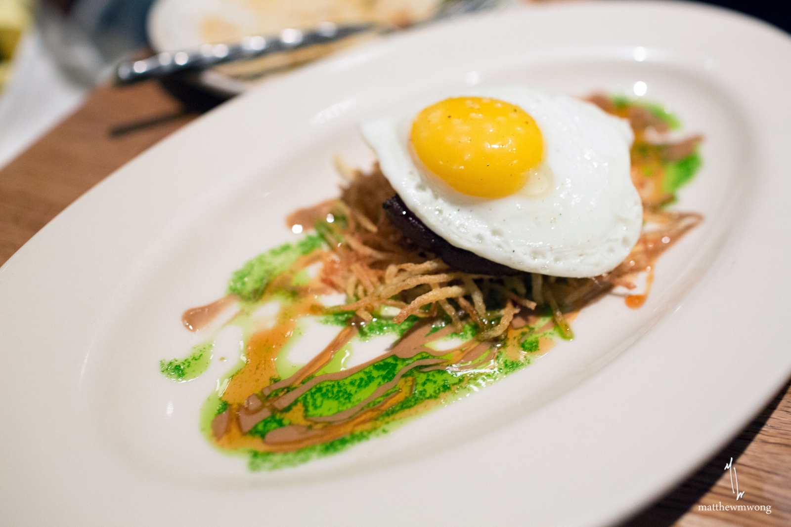 Wood oven roasted pig face, sunny side egg, tamarind, cilantro, red wine maple, potato stix